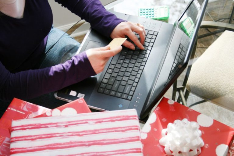 A woman holding a credit card shopping on her laptop during cyber monday surrounded by holiday gifts and other purchases