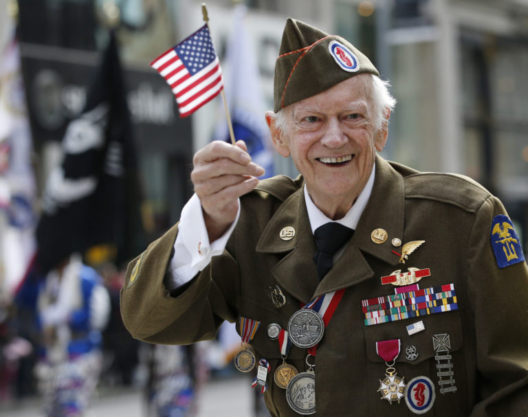 A smiling veteran, holding an American Flag while being honored on Veterans Day