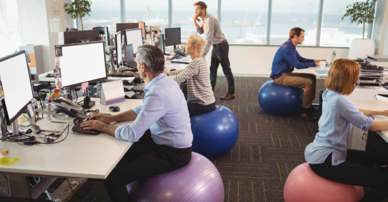 multiple employees sitting on medicine balls at their desk because of corporate wellness program being implemented because of the market increase.
