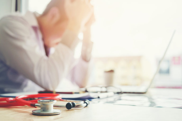 Doctor experiencing burnout with his hands on his head experiencing high levels of stress and doubt