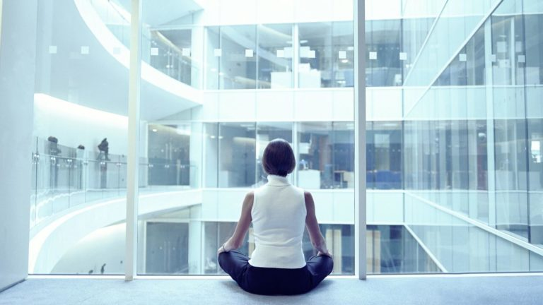Woman sitting in a yoga pose in an office building demonstrating a workplace incentive